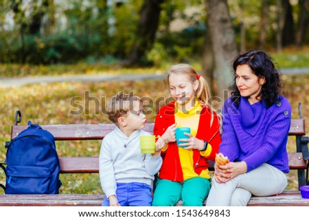 Happy mother with two laughing smiling emotional two blond children, brother and sister at autmn park. outside. Good weather concept. Family spends time together after school day. #1543649843
