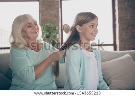 Photo of two people cute aged white haired granny little granddaughter sitting cozy sofa brushing long hairdo spending free time weekend together house indoors #1543655213