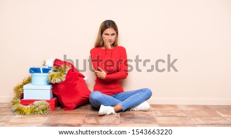 Girl in christmas holidays sitting on the floor unhappy and frustrated #1543663220