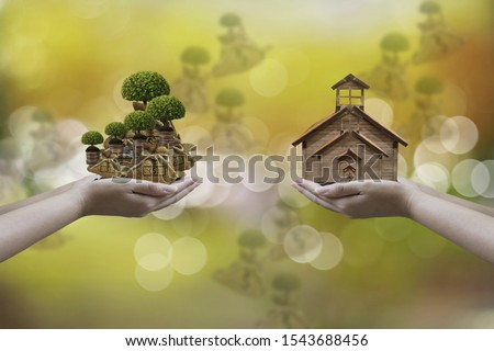 woman hand holding money bag with dollar icon,and wood house model, with blurred nature background and bokeh,concept saving money for future,investing in land and real estate and insurance #1543688456