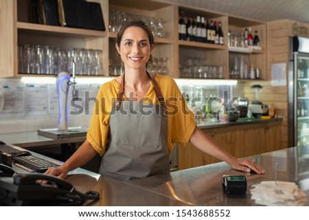 Mature woman barista standing behind the bar counter in coffee shop and looking at camera. Smiling small business owner smiling behind the counter. Portrait of beautiful waitress wearing apron. #1543688552
