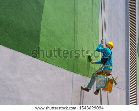 One painter is painting the exterior of the building on a dangerous looking scaffolding hanging from a tall building. #1543699094