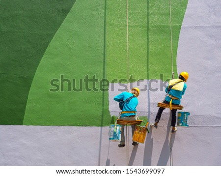 Two painters are painting the exterior of the building on a dangerous looking scaffolding hanging from a tall building with copy space. #1543699097
