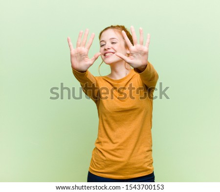 young pretty red head woman smiling and looking friendly, showing number ten or tenth with hand forward, counting down against green wall #1543700153