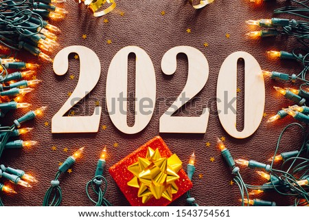 Christmas and New Year composition. 2020 simbols and garland on brown leather background. Flat lay, top view #1543754561