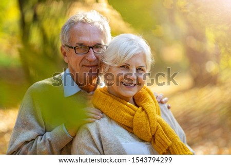 Happy senior couple in autumn park  #1543794299