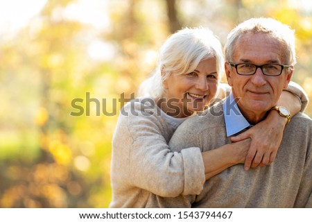 Happy senior couple in autumn park  #1543794467