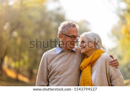 Happy senior couple in autumn park  Royalty-Free Stock Photo #1543794527