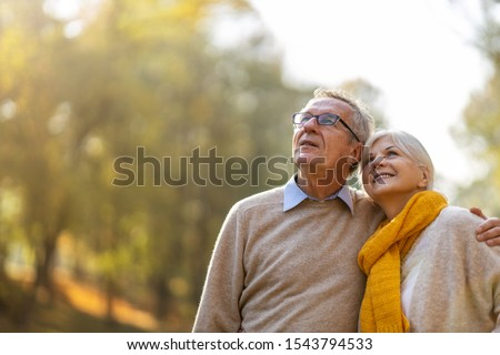 Happy senior couple in autumn park  #1543794533