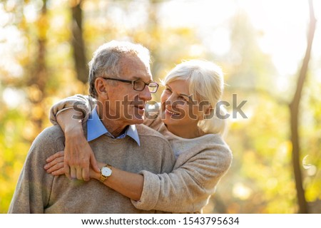 Elderly couple embracing in autumn park   #1543795634