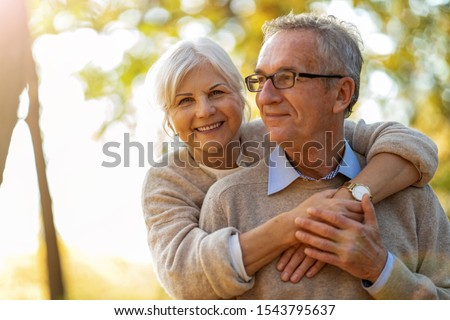 Elderly couple embracing in autumn park   #1543795637