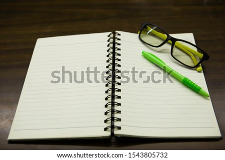 Angled, angled guide lines with notebook Yellowish-yellow surfaces, green pens and glasses on wooden floors. #1543805732
