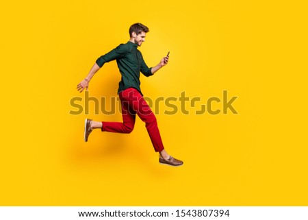 Full length profile side photo of positive cheerful guy use smartphone search discounts on social media jump run fast hurry wear green shirt red pants trousers isolated yellow color background #1543807394