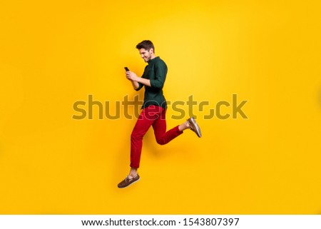 Profile side full length body size photo of cheerful positive man running jumping addicted to his cellphone aspiring for sales isolated bright color background #1543807397