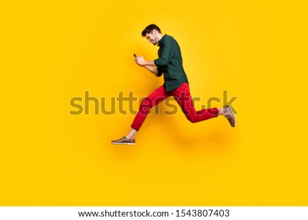 Full size profile side photo of positive cheerful brunet hair use his cellphone search find discounts jump run feel  content wear green shirt red pants trousers isolated over yellow color background #1543807403