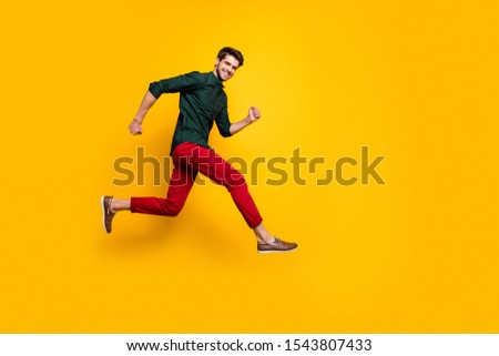 Full length body size side profile photo of cheerful positive nice handsome man in green shirt running to empty space smiling toothily isolated vibrant color background #1543807433