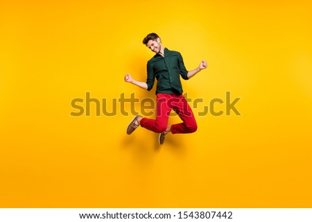 Portrait of funky crazy ecstatic guy jump feel lucky celebrate his victory in competition raise fists scream yeah wear casual style clothes sneakers isolated over yellow color background #1543807442