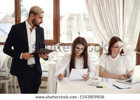 Handsome restaurant inspector with documents and two women assistants #1543809806