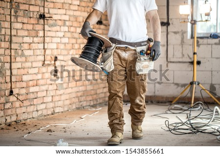 Electrician with tools, working on a construction site. Repair and handyman concept. House and house reconstruction. #1543855661