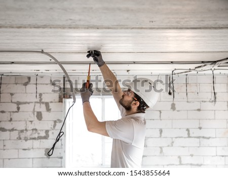 Electrician installer with a tool in his hands, working with cable on the construction site. Repair and handyman concept. House and house reconstruction. #1543855664