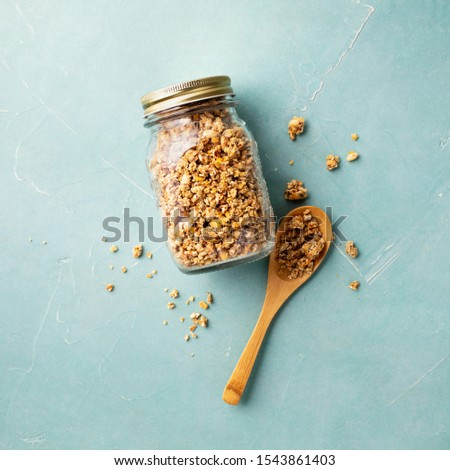 Home granola in a glass jar on blue concrete background Royalty-Free Stock Photo #1543861403