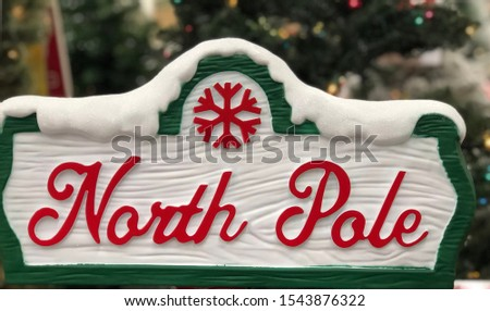 North Pole Festive Holiday sign with Lighted Christmas tree visible in the background