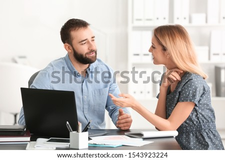 Businessman consulting young woman in office Royalty-Free Stock Photo #1543923224