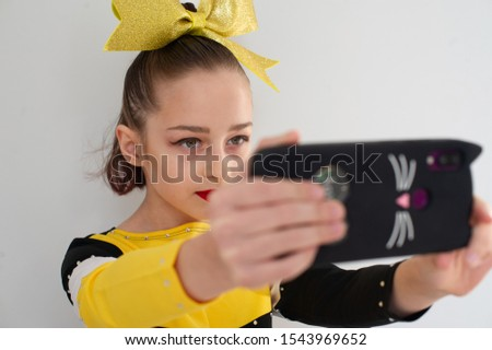 pretty girl make a self portrait with her smart phone. Girl makes a selfie. A little girl athlete makes a self portrait before her cheerleading competition. The cheerleader photographs himself