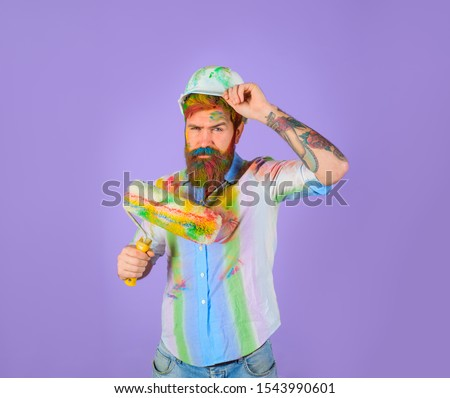 Painter man. Painter man with paint roller and helmet. Professional painter. Builder worker. Repair, building concept. Handsome bearded worker with paint roller and hard hat. Repairman, tradesman. #1543990601