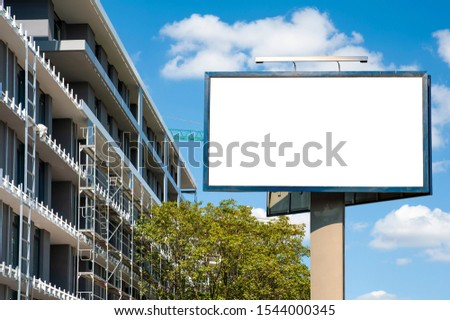 Blank white billboard mockup in front of the modern building under construction