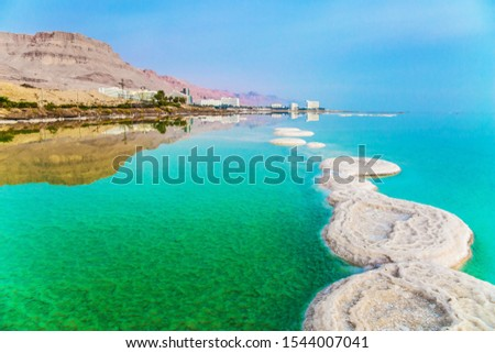 Israel. Early morning at the resorts of the Dead Sea. Azure sea water is full of healing salts. Small islets and path of salt in the water. Concept of ecological, medical and photo tourism