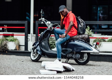 Dissatisfied young man brings best food of his restaurant, delivers pizza in cardboard boxes, has tired facial expression, uses fast motorbike to distribute fast food for customers. #1544048258