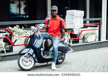 African male courier carries heavy parcel boxes, drives slowly on motorbike, wears protective helmet on head, being specialist in delivery service, distributes fast food, being tired during working da #1544048261