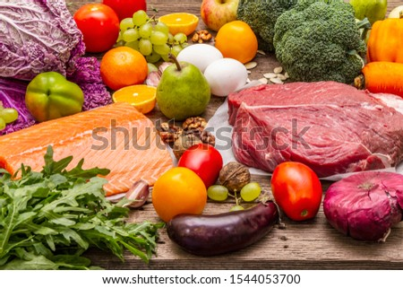Trending paleo/pegan diet. Healthy balanced food concept. Set of fresh products, raw meat, salmon, vegetables and fruits. Old wooden boards background #1544053700