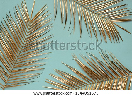 Creative arrangement of natural golden painted date palm branches on muted cyan blue background. Artistic floral luxury floral border frame design. Tropical concept. #1544061575