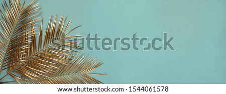 Creative arrangement of natural golden painted date palm branches on muted cyan blue background. Artistic floral luxury floral border frame design. Wide format tropical poster, banner template. #1544061578