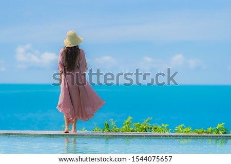 Portrait young asian woman relax smile happy around outdoor swimming pool in hotel resort with sea ocean view in holiday vacation concept #1544075657
