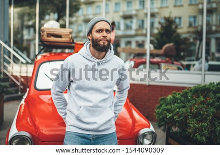 City portrait of handsome hipster man with beard wearing gray blank hoodie or sweatshirt and hat with space for your logo or design. Mockup for print