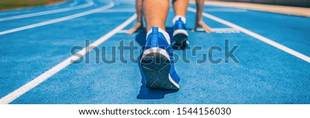 Sprinter fit man waiting for start of race on running tracks at outdoor stadium. Sport and fitness runner athlete on blue run track starting line with running shoes. Banner panorama. #1544156030