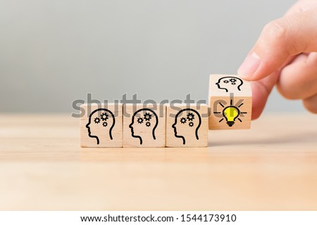 Hand flip over wooden cube block with head human symbol and light bulb icon. Concept creative idea and innovation #1544173910