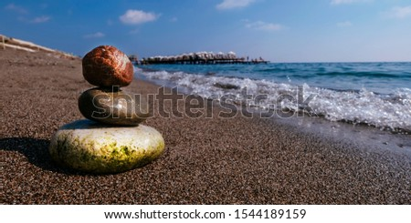 Stack of zen stones on beach near sea. Tower of spa rocks on sand at ocean. Balanced pebbles outdoors on sunny summer day. Oriental calm and harmony symbol. Wellness and tranquility concept #1544189159