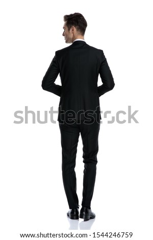 back view of young elegant in tuxedo looking to side and walking isolated on white background, full body #1544246759