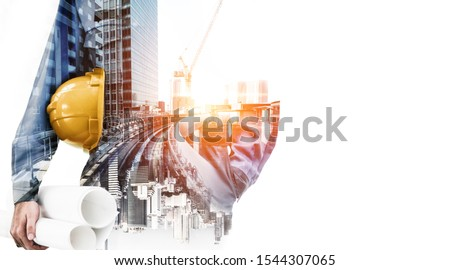 Double exposure image of construction worker holding safety helmet and construction drawing against the background of surreal construction site in the city. Royalty-Free Stock Photo #1544307065