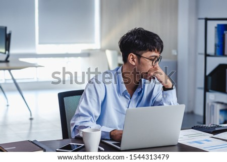 asian businessman get stress and thinking when working with laptop on desk at modern office.business fail concept.man rest hand on chin on table when stuck out of idea #1544313479