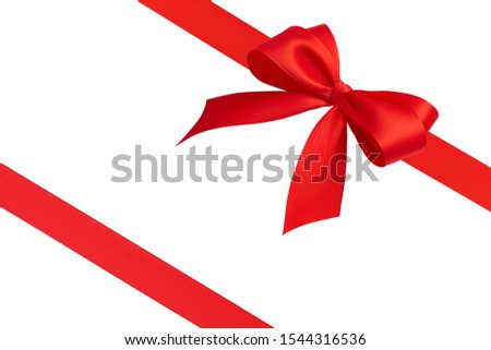 Side view of large beautiful festive handmade gift bow with four loops and two bright red diagonal silk ribbons with copy space isolated on white background. Greeting invitation discount card template #1544316536