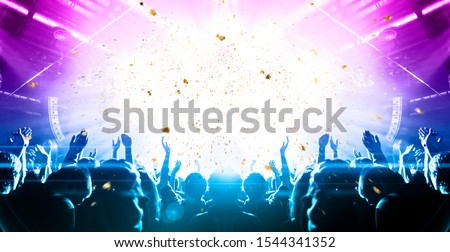 Concert hall crowded with people in front of a stage lit for the gig #1544341352