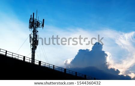 Silhouette of 5G smart mobile cellular network telephone radio network antenna base station on the telecommunication mast radiating signal. Royalty-Free Stock Photo #1544360432