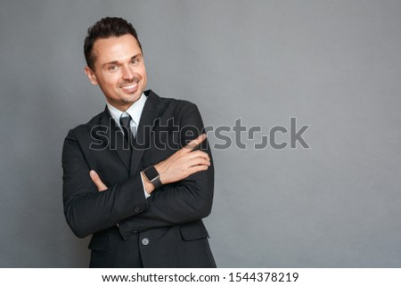 Business man studio standing isolated on grey wall crossed arms looking camera smiling playful #1544378219