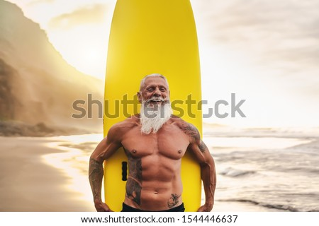 Happy fit senior having fun surfing at sunset time - Sporty bearded man training with surfboard on the beach - Elderly healthy people lifestyle and extreme sport concept #1544446637