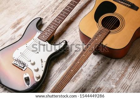 Modern guitars on wooden background